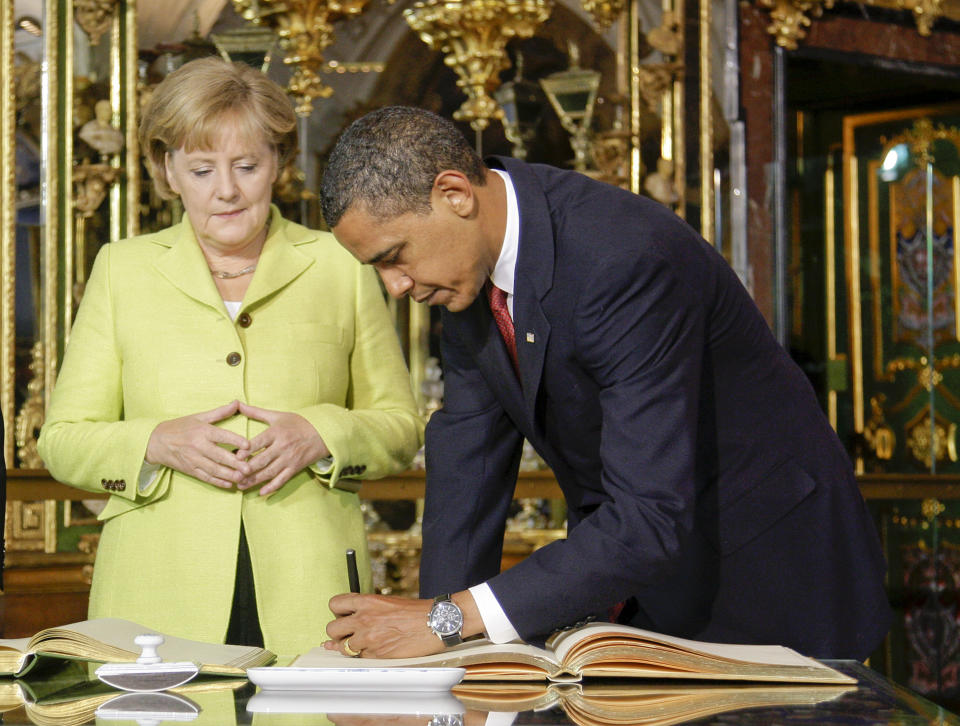 U.S. President Barack Obama signs the golden book next to German Chancellor Angela Merkel inside the Gruenes Gewoelbe  (Green Vault) at the Royal Palace in the eastern German city of Dresden, June 5, 2009. Obama arrived to  the eastern city of Dresden, which was destroyed by U.S. and British bombers in the closing months of the war.  Obama will also tour the former Buchenwald concentration camp to commemorate victims of the Holocaust with Chancellor Angela Merkel.  REUTERS/Tobias Schwarz     (GERMANY)