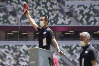 """An official wearing a face mask uses a starter pistol to signal the start a women's 100 meter heat at an athletics test event for the Tokyo 2020 Olympics Games at National Stadium in Tokyo, Sunday, May 9, 2021. The competition entitled: """"Ready Steady Tokyo - Athletics."""" (AP Photo/Shuji Kajiyama)"""