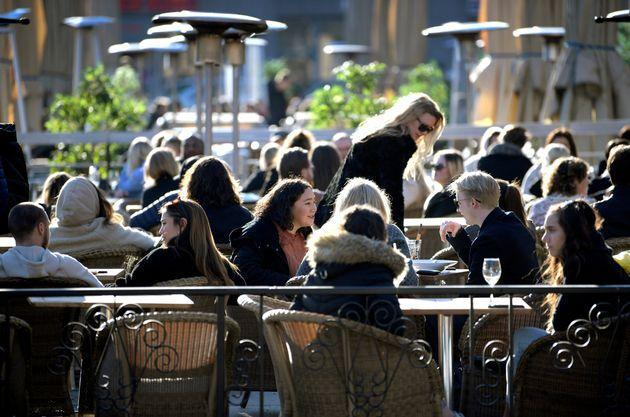 People enjoy the sun at an outdoor restaurant, despite the continuing spread of the coronavirus disease in Stockholm, Sweden March 26.