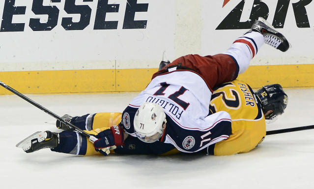 Columbus Blue Jackets left wing Nick Foligno (71) falls on Nashville Predators forward Mike Fisher (12) after chasing down the puck in the first period of an NHL hockey game on Saturday, March 8, 2014, in Nashville, Tenn. (AP Photo/Mark Zaleski)