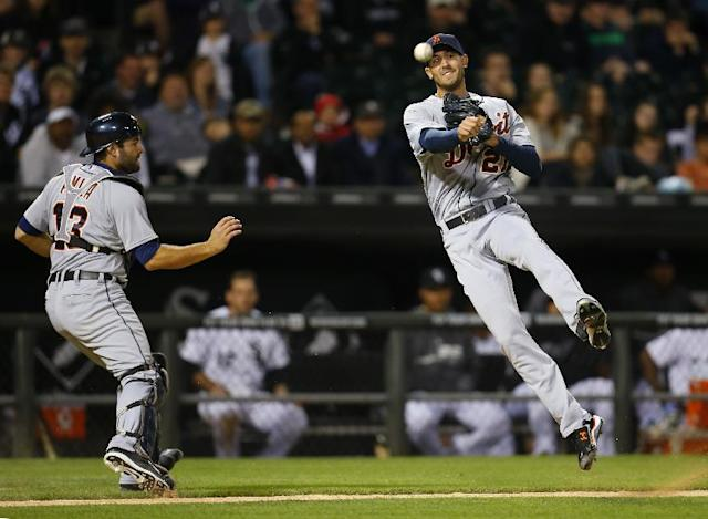 Detroit Tigers starting pitcher Rick Porcello (21) throws to first off a bunt as catcher Alex Avila (13) watches during the sixth inning of a baseball game against the Chicago White Sox on Monday, June 9, 2014, in Chicago. (AP Photo/Jeff Haynes)