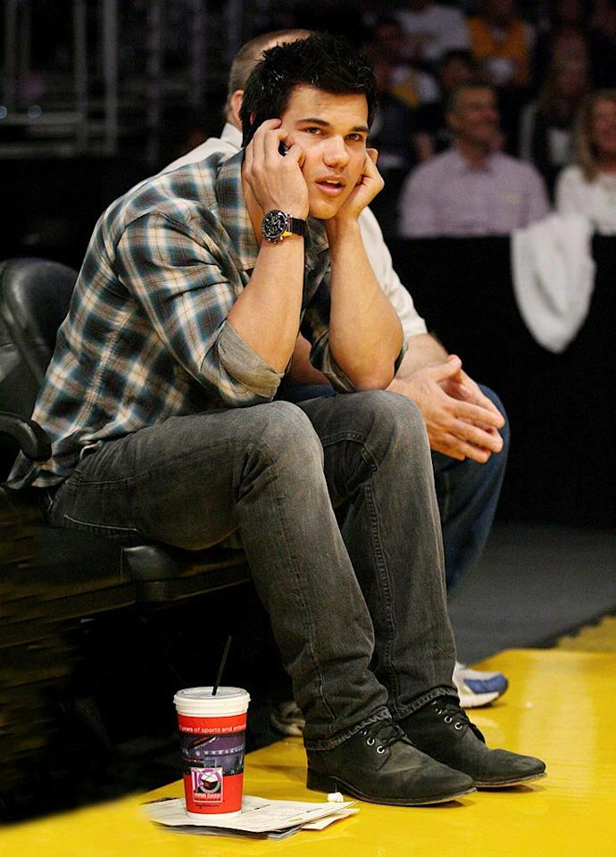 "Taylor Lautner was busy phoning it in at LA's Staples Center on Easter Sunday, where the San Antonio Spurs defeated the Los Angeles Lakers 100-81. London Ent/<a href=""http://www.splashnewsonline.com"" target=""new"">Splash News</a> - April 4, 2010"
