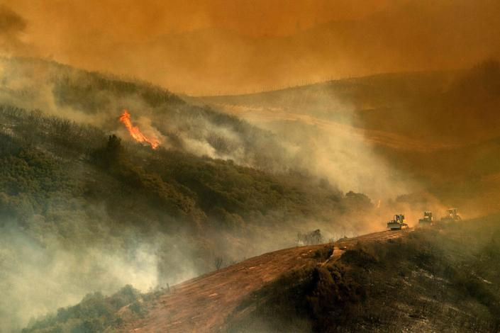 Bulldozer operators and their machines build containment lines while battling the River Fire.