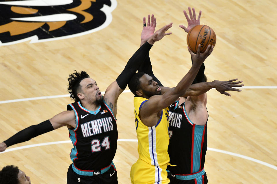 Golden State Warriors forward Andrew Wiggins shoots against Memphis Grizzlies forward Dillon Brooks (24) and center Jonas Valanciunas in the second half of an NBA basketball game Saturday, March 20, 2021, in Memphis, Tenn. (AP Photo/Brandon Dill)