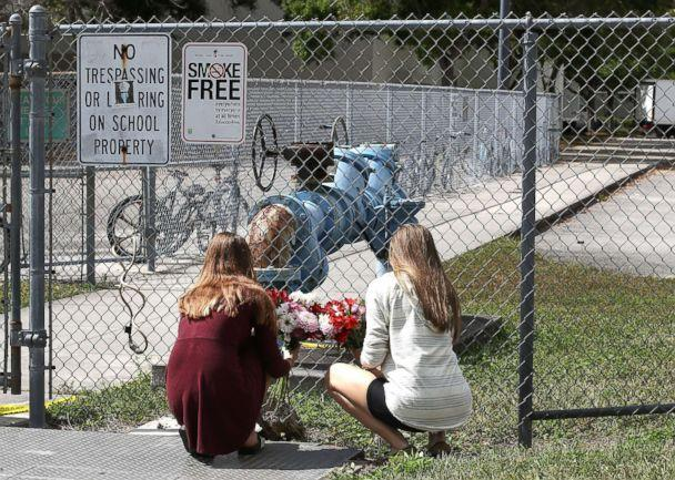 PHOTO: Students Jessica Garagro (L) and Sarah Goodchild, place flowers at a fence that surrounds Marjory Stoneman Douglas High School, Feb. 18, 2018 in Parkland, Fla. (Mark Wilson/Getty Images)