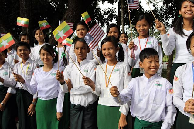 Myanmar students wave Myanmar and U.S. flags as they wait to welcome the arrival of U.S. President Barack Obama at Yangon International Airport Monday, Nov. 19, 2012, in Yangon, Myanmar. (AP Photo/Khin Maung Win)