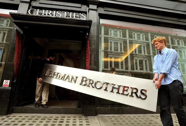 Christie's employees walk into the auction rooms with the main sign from the Lehman Brothers London office after the bank collapsed.