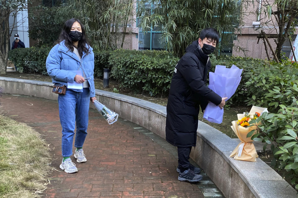 "Residents visiting the Wuhan Central Hospital offer flowers in memory of Li Wenliang, the whistleblower doctor who sounded the alarm and was reprimanded by local police for it in the early days of Wuhan's pandemic, prior to the anniversary of his death, in central China's Hubei province, Saturday, Feb. 6, 2021. Dr. Li Wenliang died in the early hours of Feb. 7 from the virus first detected in this Chinese city. A small stream of people marked the anniversary at the hospital. The 34-year-old became a beloved figure and a potent symbol in China after it was revealed that he was one the whistleblowers who authorities had punished early for ""spreading rumors"" about a SARS-like virus. (AP Photo/Ng Han Guan)"