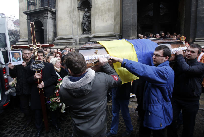 People carry the coffin of Bogdan Solchunuk, in front of the St. Paul and Peter church, during his funeral, in Lviv, western Ukraine, Saturday, Feb. 22, 2014. Church services were held Saturday in the pro-opposition stronghold of Lviv in the west of Ukraine for the locals who were killed in Kiev during the past week. Lviv activists say 19 of their people were killed in the violence at Maidan. (AP Photo/Darko Vojinovic)