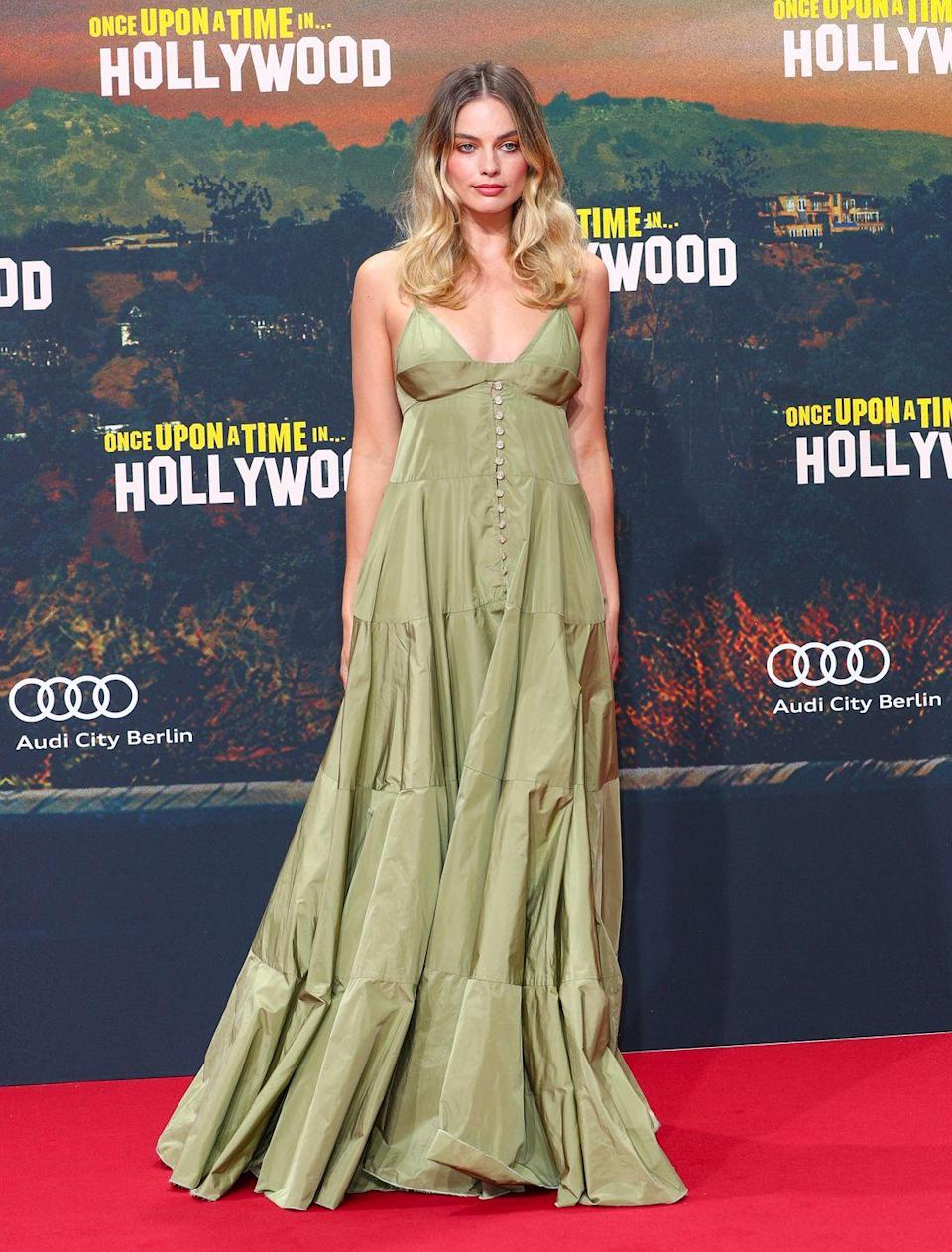"""<p>It's evident (we mean, see below) that Margot Robbie has been slaying the Once Upon A Time In Hollywood publicity tour when it comes to her outfit choices. Her most recent gown was a green tiered strap dress by Jacquemus, which was fresh off the runway having <a href=""""https://www.elle.com/uk/fashion/a28178761/jacquemus-ss20-show/"""" rel=""""nofollow noopener"""" target=""""_blank"""" data-ylk=""""slk:featured in the brand's internet-breaking anniversary show held in a lavender field."""" class=""""link rapid-noclick-resp"""">featured in the brand's internet-breaking anniversary show held in a lavender field.</a></p>"""