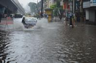 Motorists drive through a flooded road in Mumbai. (Photo by Arun Patil)