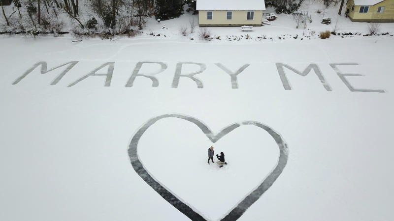 In this Jan. 7, 2018 photo provided by Ed Becker, Gavin Becker proposes to his long-time girlfriend Olivia Toft on Eight Crow Wing Lake near Nevis, Minn. Becker had his family's help etching out the big question with a snow blower in 25-foot-tall letters and a huge heart in the snow on the frozen lake. Then Gavin rented a plane and took Toft, who said yes, for a ride over the lake to see where his father took photos of the event. (Ed Becker via AP)
