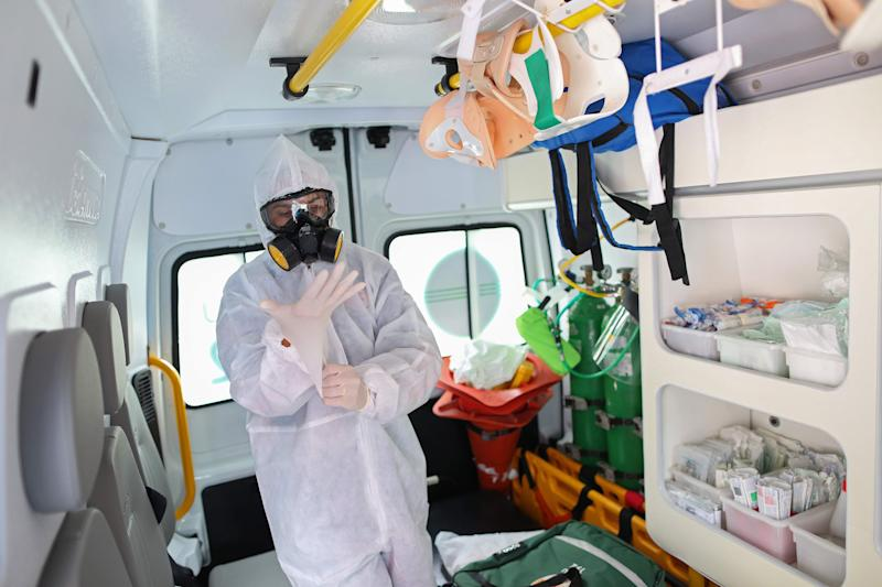 A member of the emergency medical service SAMU puts gloves on as they transport a patient suspected of being infected with the novel coronavirus COVID-19, to the hospital in Manaus, Brazil, on May 5, 2020. (Photo by MICHAEL DANTAS / AFP) (Photo by MICHAEL DANTAS/AFP via Getty Images)