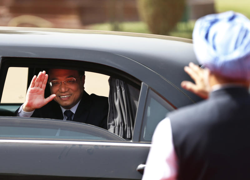 Chinese Premier Li Keqiang waves to Indian Prime Minister Manmohan Singh, right, as he leaves the Indian Presidential Palace after his ceremonial reception in New Delhi, India, Monday, May 20, 2013. Just weeks after a tense border standoff, Li visited India on his first foreign three-day trip as the neighboring giants look to speed up efforts to settle a decades-old boundary dispute and boost economic ties. (AP Photo/Saurabh Das)