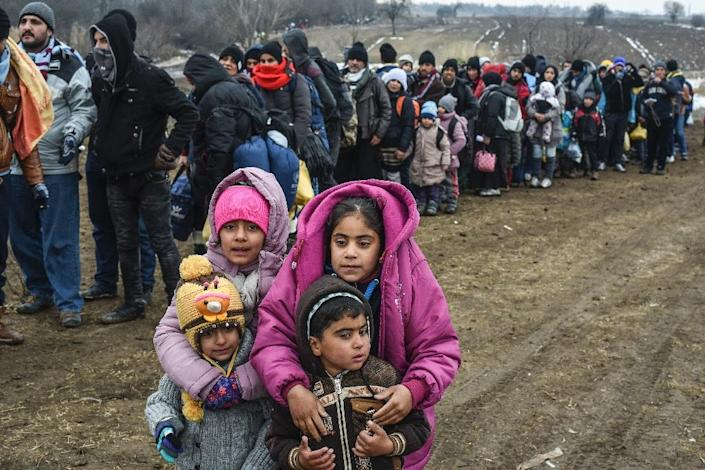 Children pose as they wait with other migrants and refugees in line for a security check after crossing the Macedonian border into Serbia, near the village of Miratovac, on January 26, 2016 (AFP Photo/Armend Nimani)