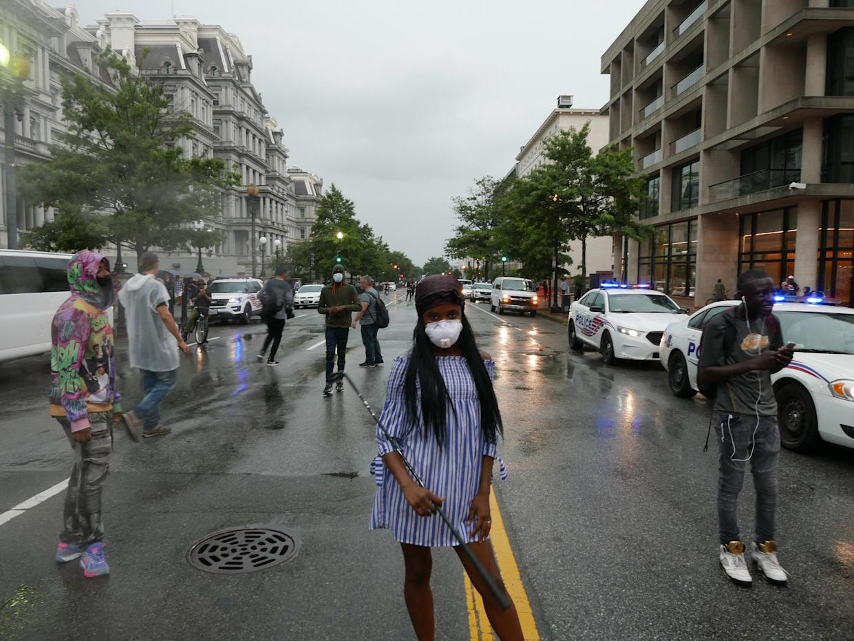 A masked counterprotester holds a golf club. (Photo: Hunter Walker/Yahoo News)