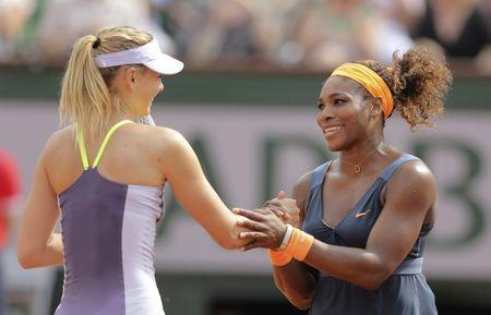 Serena Williams of the U.S. shakes hands with Maria Sharapova (L) of Russia after winning their women's singles final match at the French Open tennis tournament at the Roland Garros stadium in Paris June 8, 2013. Serena Williams proved an irresistible force once more as she powered past Maria Sharapova 6-4 6-4 to win the French Open for the second time on Saturday - 11 years after her first triumph. REUTERS/Stephane Mahe