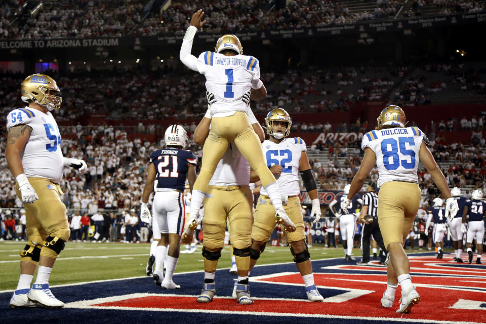 UCLA quarterback Dorian Thompson-Robinson (1) is hoisted after his rushing touchdown during the third quarter against Arizona in an NCAA college football game Saturday, Oct. 9, 2021, in Tucson, Ariz. (AP Photo/Chris Coduto)