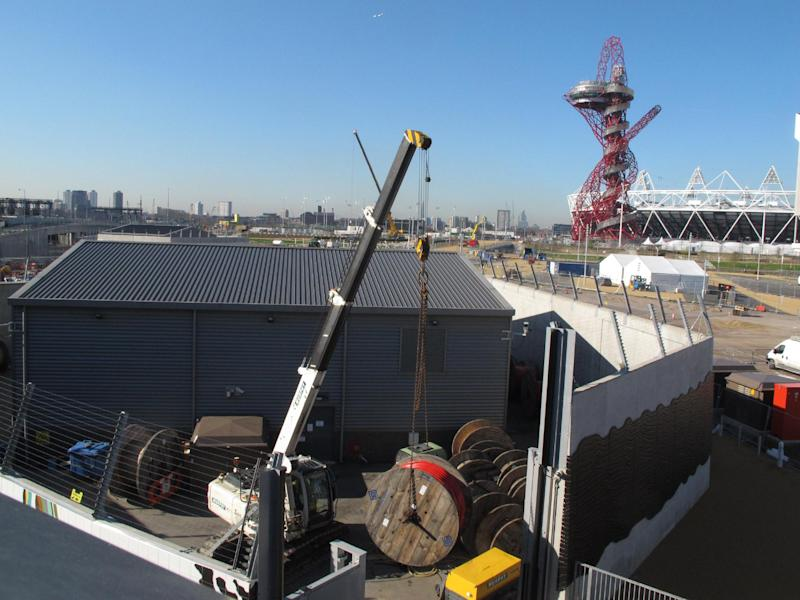 A crane hoists a spool of cabling at London's Olympic Park on Monday, March 19, 2012. Those responsible for the British capital's network of fiber optic cables, phone masts and wifi hotspots say they're bracing for a data deluge as the games get underway. (AP Photo/Raphael Satter)