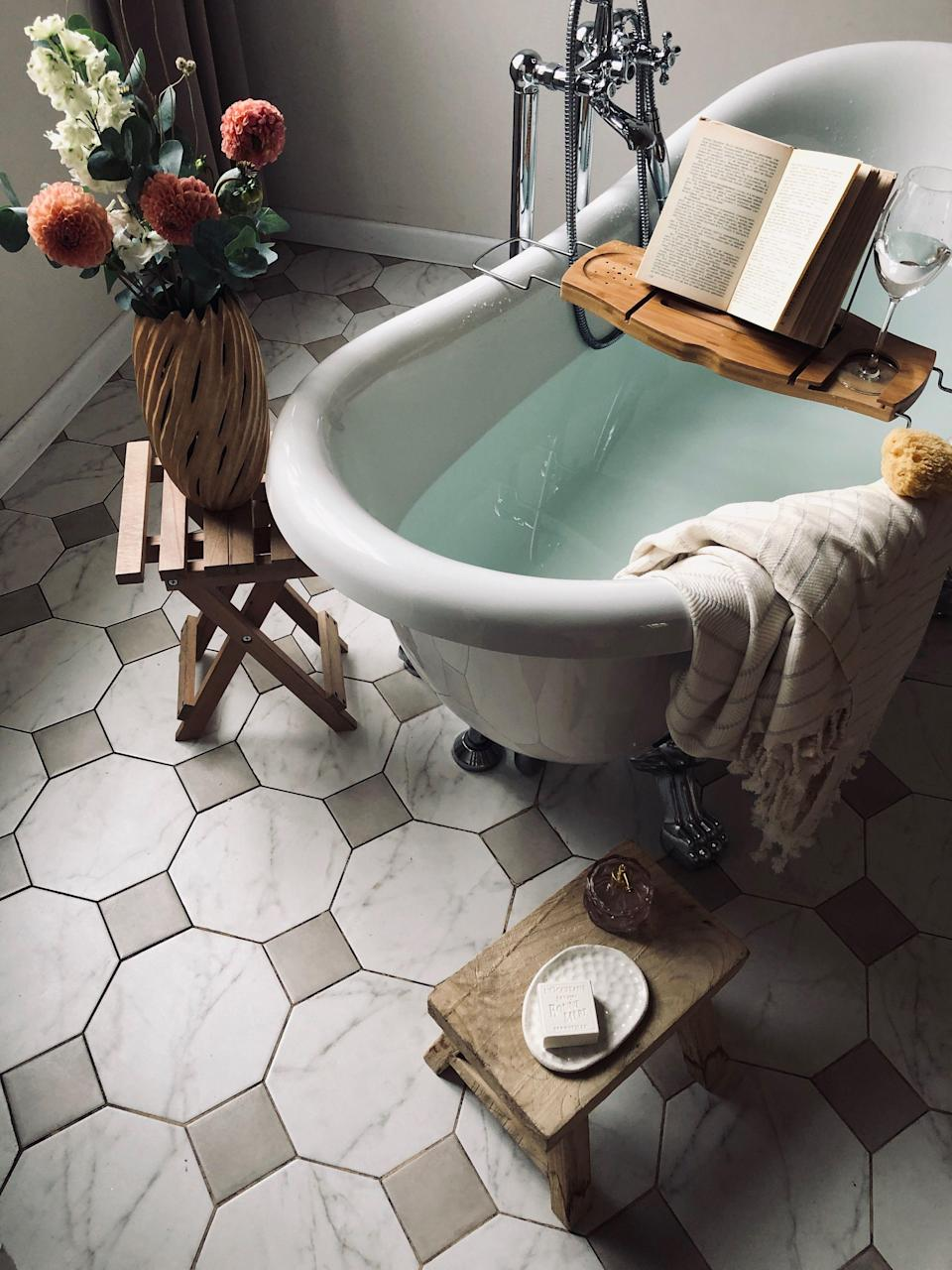 """<p>It's been a long week, so you draw a <a href=""""https://www.oprahdaily.com/beauty/g26976206/best-bubble-bath/"""" rel=""""nofollow noopener"""" target=""""_blank"""" data-ylk=""""slk:warm bubble bath"""" class=""""link rapid-noclick-resp"""">warm bubble bath</a>. A <a href=""""https://www.oprahdaily.com/life/g36055948/summer-candles/"""" rel=""""nofollow noopener"""" target=""""_blank"""" data-ylk=""""slk:heavenly scented candle"""" class=""""link rapid-noclick-resp"""">heavenly scented candle</a> is burning as you put on your <a href=""""https://www.oprahdaily.com/beauty/g34764304/best-spa-headbands/"""" rel=""""nofollow noopener"""" target=""""_blank"""" data-ylk=""""slk:spa headband"""" class=""""link rapid-noclick-resp"""">spa headband</a> and submerge into the water. But, as soon as you do, you realize you forgot your <a href=""""https://www.oprahdaily.com/life/food/g27412334/cheap-wine-brands/"""" rel=""""nofollow noopener"""" target=""""_blank"""" data-ylk=""""slk:glass of wine"""" class=""""link rapid-noclick-resp"""">glass of wine</a> and there's nowhere to prop up your <a href=""""https://www.oprahdaily.com/entertainment/books/g32909485/best-books-about-summer-romance/"""" rel=""""nofollow noopener"""" target=""""_blank"""" data-ylk=""""slk:juicy new romance novel"""" class=""""link rapid-noclick-resp"""">juicy new romance novel</a>. Sounds like it's finally time to get a bathtub tray. </p><p>Designed to rest over your tub, a bathtub trays keep your self-care essentials within reach as you soak. Many function as caddies with organizational compartments for soap, a loofah, your washcloth, a great book, and of course, that aforementioned glass of wine. A classic wooden teak or bamboo board contributes to the zen vibe and looks beautiful over a freestanding vessel—even when it's not in use. Adjustable metal or plastic caddies and even swivel trays are convenient as well, especially for smaller tubs or ones that sit against a wall (they also make for easy storage). <br></p><p>No matter your preference, these will all help you <a href=""""https://www.oprahdaily.com/life/a35843899/oprah-bathtub-routine/"""" rel"""