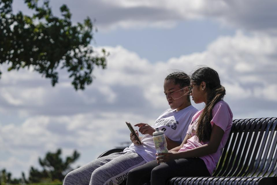 Savannah Brown and Glendy Stollberg use their phone in Kilbourn Reservoir Park Wednesday, Sept. 8, 2021, in Milwaukee. The City of Milwaukee has placed wireless broadband hotspots in the park during the pandemic. (AP Photo/Morry Gash)