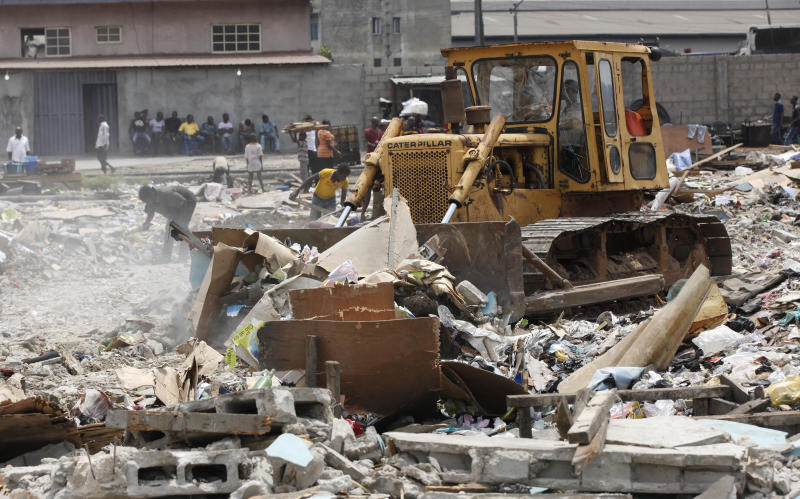 In this image taken Thursday Feb. 28, 2013 a bulldozer levels the site of demolished houses at Ijora Badia slum in Lagos, Nigeria. The bulldozers arrived at dawn to this neighborhood of shanty homes and concrete buildings in Nigeria's largest city, followed by police officers in riot gear carrying Kalashnikov assault rifles. The police banged on doors, corralling the thousands who live in Ijora-Badia off to the side as the bulldozers' blades tore through scrap-lumber walls, its track grinding the possessions inside into the black murk of swamp beneath it. It left behind only a field of debris that children days later picked through, their small hands dodging exposed rusty nails to pull away anything of value left behind. (AP Photo/Sunday Alamba)