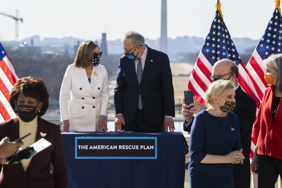 UNITED STATES - MARCH 10: From left, Rep. Maxine Waters, D-Calif., Speaker of the House Nancy Pelosi, D-Calif., Senate Majority Leader Chuck Schumer, D-N.Y., Reps. Carolyn Maloney, D-N.Y., Jim McGovern, D-Mass., and Katherine Clark, D-Mass., attend a bill enrollment ceremony for the American Rescue Plan Act on the West Front of the Capitol after the House passed the $1.9 trillion covid-19 relief package on Wednesday, March 10, 2021. (Photo By Tom Williams/CQ-Roll Call, Inc via Getty Images)