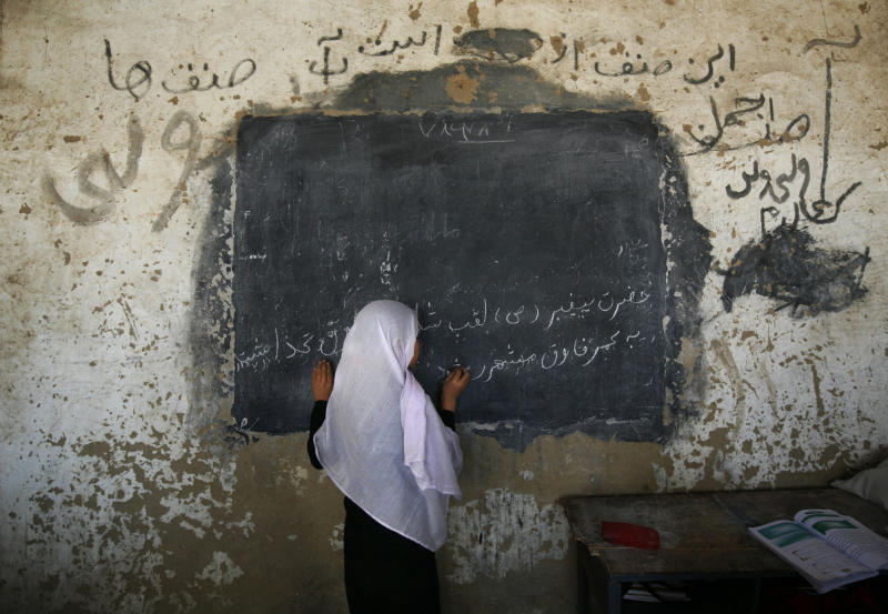 FILE - In this Sunday, Sept. 21, 2008 file photo, an Afghan girl writes on a board in front her class at the girls high school Ayeshe Sedeqa in the center of Kunduz, northern Afghanistan. The Afghan government alleges the Taliban tried to poison students at girls' schools, causing outbreaks of sickness, and says 15 suspects have been arrested. (AP Photo/Anja Niedringhaus, File)