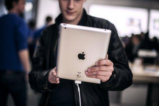 Photo illustration shows a customer in Lyon, France, holding an Apple iPad. The US tech giant has paid $60 million to end a dispute over who could use the iPad name in China, a court said Monday, giving Apple more certainty in selling its tablet computer in the Chinese market