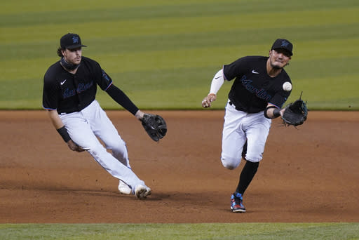 Miami Marlins shortstop Miguel Rojas, right, fields a ball hit by Washington Nationals' Asdrubal Cabrera, who was out at first, as third baseman Brian Anderson watches during the first inning of the second game of a baseball doubleheader, Friday, Sept. 18, 2020, in Miami. (AP Photo/Wilfredo Lee)