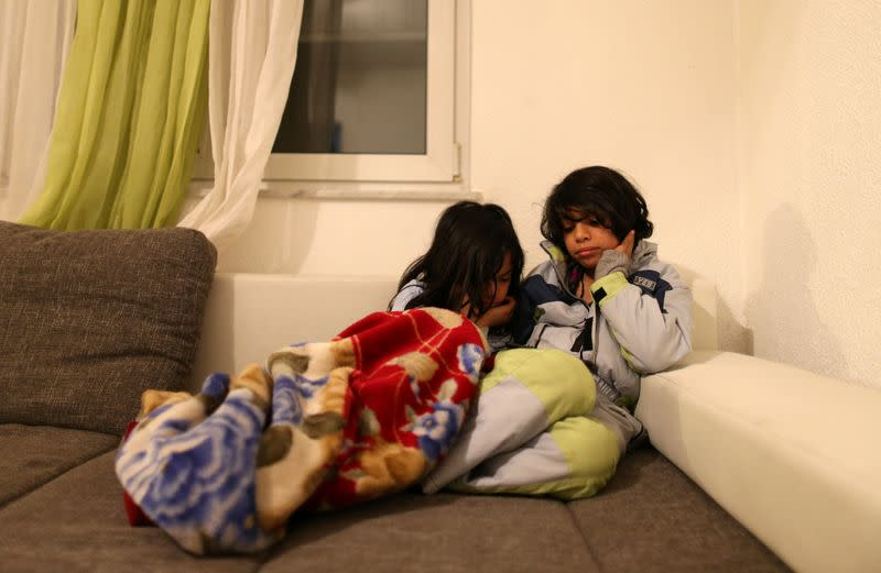 Two brothers from Iraq Hsan and Hubas watch cartoons in their temporary home in a village near Velika Kladusa