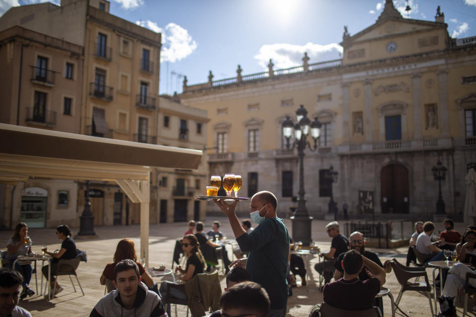 FILE - In this Monday, May 11, 2020 file photo, a waiter carries beers for customers sitting at a terrace bar in Tarragona, Spain. The European Union announced Tuesday, June 30, 2020 that it will reopen its borders to travelers from 14 countries, but most Americans have been refused entry for at least another two weeks due to soaring coronavirus infections in the U.S. (AP Photo/Emilio Morenatti, File)