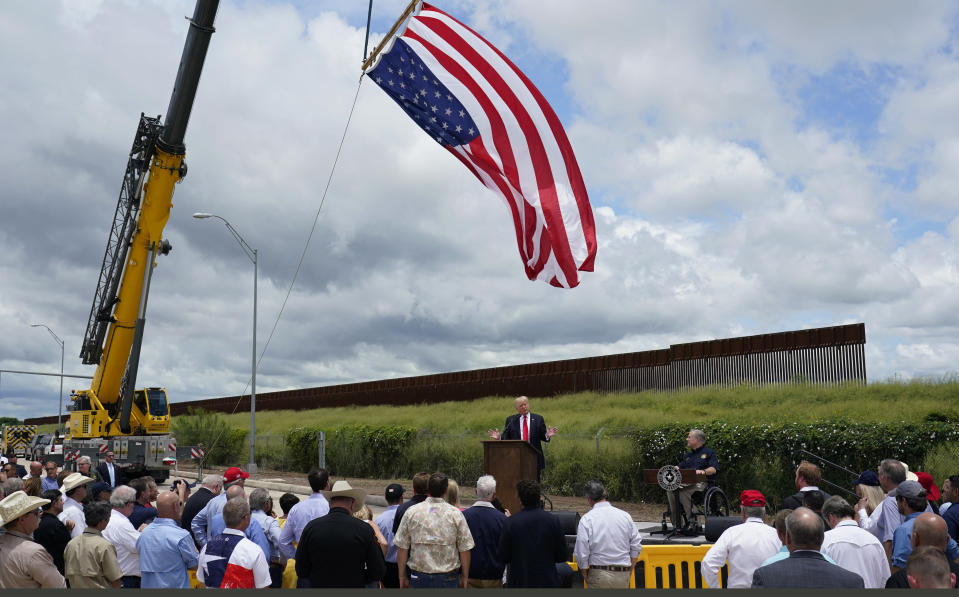Former President Donald Trump, left, and Texas Gov. Greg Abbott, right, speak during a stop at an unfinished section of border wall, in Pharr, Texas, Wednesday, June 30, 2021. (AP Photo/Eric Gay)