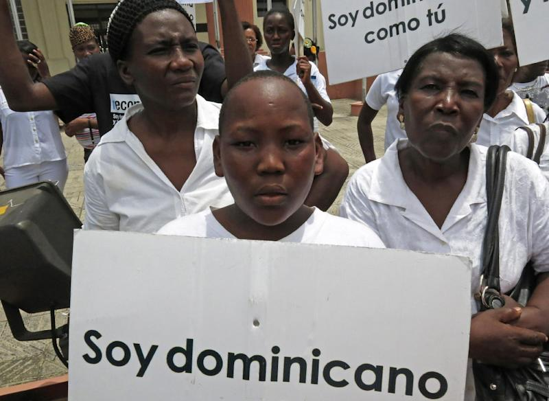 "FILE - In this Aug. 12, 2013 file photo, a youth of Haitian descent holds a sign that reads in Spanish ""I'm Dominican"" during a protest demanding that President Danilo Medina stop the process to invalidate their birth certificates after authorities retained their ID cards, in Santo Domingo, Dominican Republic. The Dominican Republic's top court on Thursday, Sept. 26, 2013 stripped citizenship from thousands of people born to migrants who came illegally, a category that overwhelmingly includes Haitians brought in to work on farms. The decision cannot be appealed, and it affects all those born since 1929. (AP Photo/Ezequiel Abiu Lopez, File)"