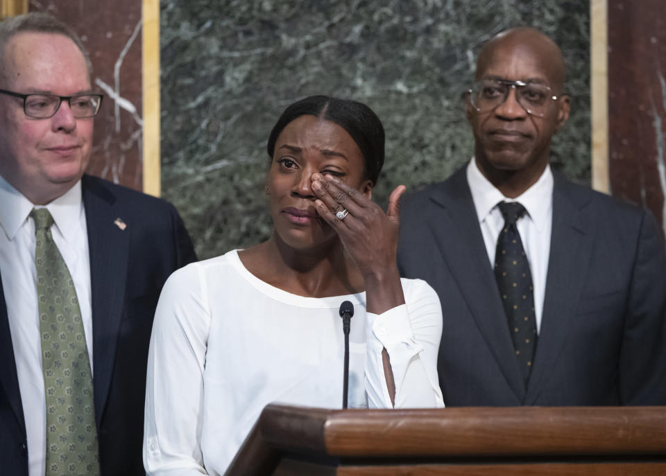 FILE - In this Oct. 31, 2018, file photo, Alysia Montano is flanked by Jim Carroll, deputy director of the Office of National Drug Control Policy, left, and Edwin Moses, chairman of the U.S. Anti-Doping Agency, as she wipes away tears as she recounts her experience finishing behind two Russian runners using performance-enhancing drugs, during a White House event aimed at reforming the World Anti-Doping Agency, in Washington. On Monday, Sept. 30, 2019, Montano walked off the track at the World Championships in Doha, Qatar, with a pair of bronze medals that were placed around her neck several years too late. The U.S. 800-meter runner who has stood up on behalf of every athlete who has ever kept off the medals stand by a doper finally got the third-place prizes she was robbed of at two straight worlds, back in 2011 and 2013. (AP Photo/J. Scott Applewhite, File)