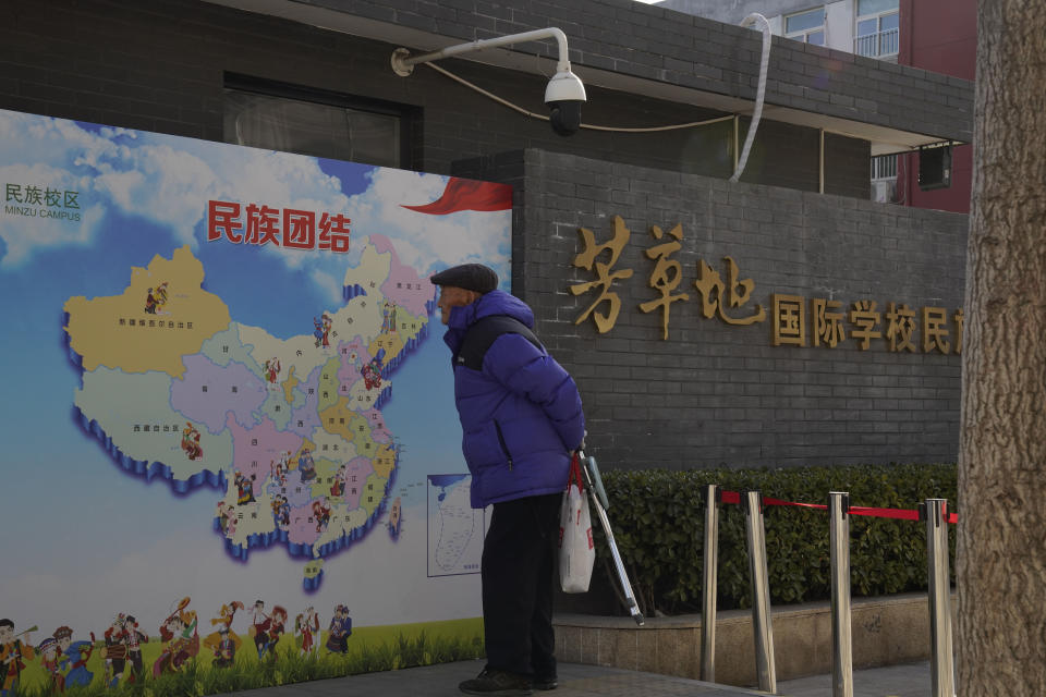 "An elderly Chinese man looks at map of Chinese showing its different ethnic groups and the slogan ""Ethnic Unity"" in Beijing, China Monday, Jan. 11, 2021. A Chinese official on Monday denied Beijing has imposed coercive birth control measures among Muslim minority women, following an outcry over a tweet by the Chinese Embassy in Washington claiming that government polices had freed women of the Uighur ethnic group from being ""baby-making machines."" (AP Photo/Ng Han Guan)"