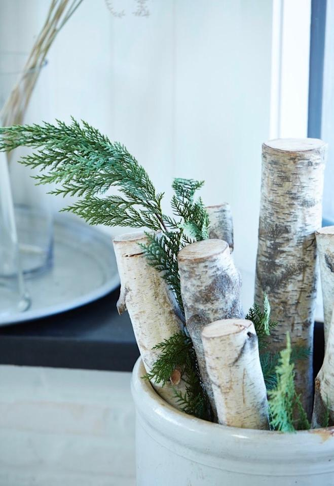 "<p>A few embellished birch logs can go a long way when you're looking for simple, easy ways to decorating your home for the holidays. ""Add cedar sprigs to a basket of logs to make a simple but elegant holiday statement,"" Swift says. ""Or, wrap a birch log in a bow and use a fabric marker to write your family's name on the ribbon to personalize it.""</p>"