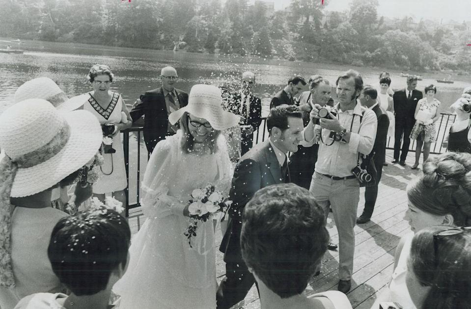 """<p>This lovely outdoor ceremony took place by a lake, an always-lovely place to tie the knot. We imagine that the bride's hat came in handy for shielding her face from the glare of the sun. (Chalk up another """"pro"""" to wearing a wedding chapeau.) </p>"""