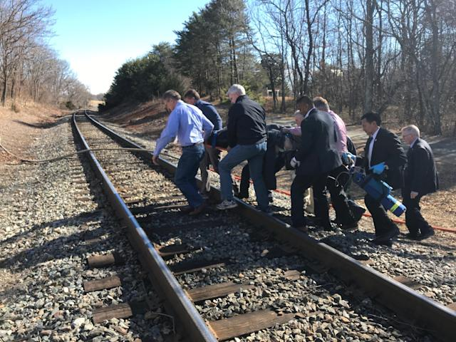 <p>Emergency first responders and passengers from an Amtrak passenger train carrying Republican members of the U.S. Congress from Washington to a retreat in West Virginia carry one of the injured across train tracks to an ambulance after the train collided with a garbage truck in Crozet, Va. on Jan. 31, 2018. (Photo: Justin Ide/Crozet Volunteer Fire Department/Reuters) </p>