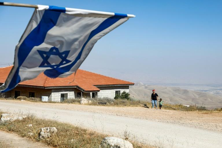 An Israeli flag flies over the wildcat settlement outpost of Givat Arnon, one of 70 the settler lobby is pressing Prime Minister Bejamin Netanyahu to commit to recognising in return for its support