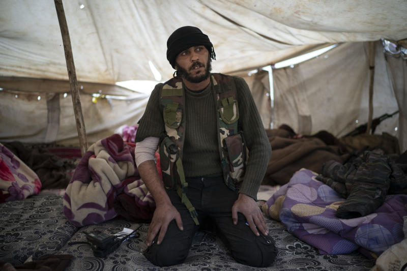 A U.S.-backed Syrian Democratic Forces (SDF) fighter sits inside a tent atop a hill in the desert outside the village of Baghouz, Syria, Thursday, Feb. 14, 2019. U.S.-backed Syrian forces are clearing two villages in eastern Syria of remaining Islamic State militants who are hiding among the local population, and detaining others attempting to flee with the civilians, the U.S.-led coalition said Thursday. (AP Photo/Felipe Dana)
