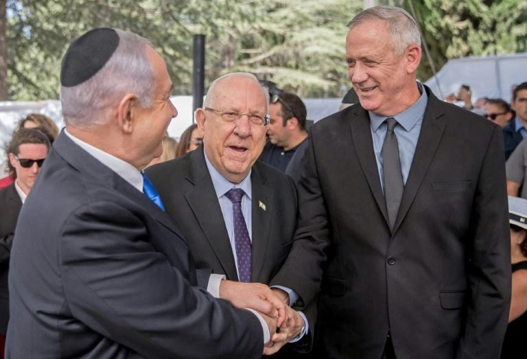 Israel President Reuven Rivlin watches on as opposition leader Benny Gantz shakes hands with Prime Minister Benjamin Netanyahu hours before laying claim to his job