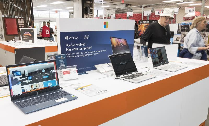 Customers pass by laptops on display at a Costco Club store in Waltham, Massachusetts, USA 13 August 2019. Earlier oil the day United States President Donald J Trump announced the exemption on selected Chinese goods, including telephones, television, footwear, clothing and laptop computers from upcoming new rounds of tarifs through December 2019. EFE/EPA/CJ GUNTHER
