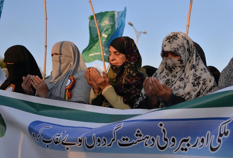 Women supporters of Pakistani party Jammat-e-Islami (JI) pray for the victims of the Peshawar school massacre, during a rally in Islamabad on December 26, 2014