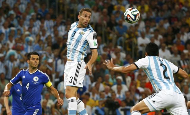 Argentina's Hugo Campagnaro reaches for the ball during their 2014 World Cup Group F soccer match against Bosnia at the Maracana stadium in Rio de Janeiro June 15, 2014. REUTERS/Michael Dalder (BRAZIL - Tags: SOCCER SPORT WORLD CUP)