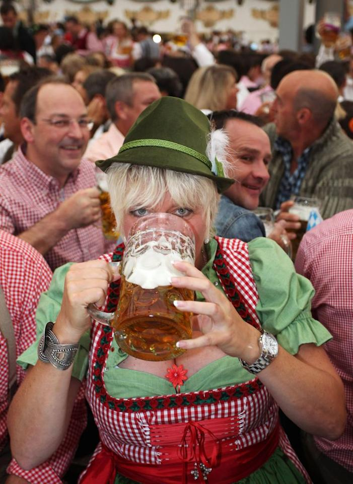 A woman wears a traditional Bavarian Dirndl dress as she drinks beer in a beer tent at the Oktoberfest 2012.