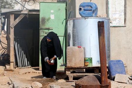 A Palestinian woman washes a pot from a tank outside her house on the outskirts of the West Bank village of Yatta, south of Hebron, August 17, 2016. REUTERS/Mussa Qawasma