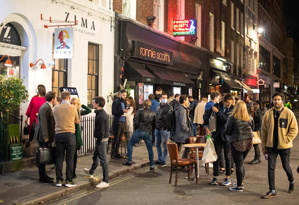 People leave bars and restaturants at closing time in Soho, London, the day after pubs and restaurants were subject to a 10pm curfew to combat the rise in coronavirus cases in England. (Photo by Dominic Lipinski/PA Images via Getty Images)