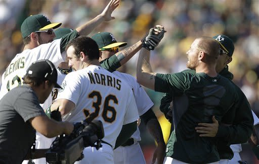 Oakland Athletics' Brandon Moss, right, is congratulated by teammates after hitting the game-winning three-run home run in the 10th inning of a baseball game against the Seattle Mariners on Saturday, Sept. 29, 2012, in Oakland, Calif. (AP Photo/Ben Margot)