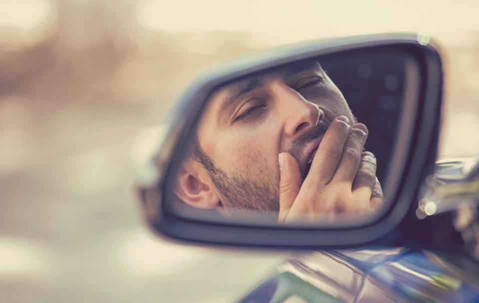 sleepy tired fatigued yawning exhausted young man driving his car